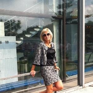 Blonde Frau um die 40 mit Sonnenbrille im Rock lehnt an Geländer